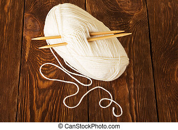 Hank of soft yarn and wooden knitting needles, on table -...