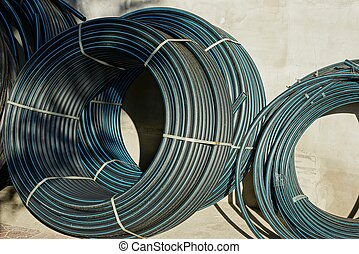 hanks of black plastic pipes against a gray wall in the street