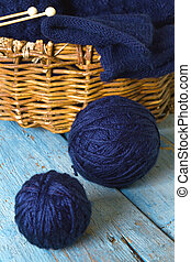 Hanks of wool, knitting needles and blue knitted scarf