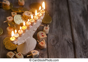 Jewish holiday hannukah symbols - menorah and wooden dreidels. Copy space background.