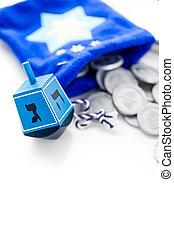 Hanukkah - Blue dreidel with silver tokens on a white...
