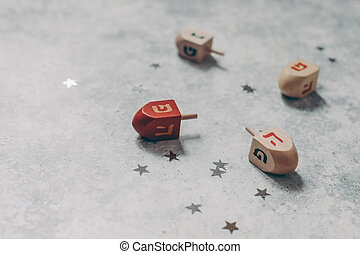 Hanukkah holiday concept. Closeup of wooden dreidel toys, golden and silver confetti stars decoration on grunge concrete background. Jewish holiday design. Empty copy space, selective focus.