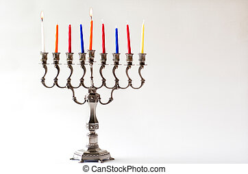 Lit Hanukkah menorah during the first day of the Jewish holiday of Hanukkah. close up