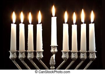 Silver Hanukkah candles all candle lite on the traditional Hanukkah menorah