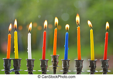 Hanukkah menorah lit with eight candles at the last day of...