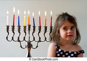 Hanukkah menorah - Cute Jewish girl look at fully lit...
