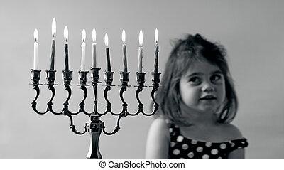 Hanukkah menorah - Jewish girl look at fully lit Hanukkah...