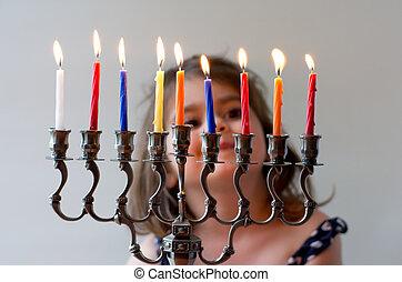 Hanukkah menorah - Happy Jewish girl look at fully lit...