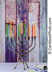 Hanukkah menorah with burning candles on wooden table front old vintage concrete wall background.