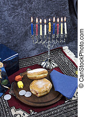 Hanukkah Menorah with lit Candles, Gifts, Dreidel and Jelly Filled Pastry