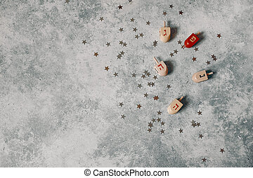 Hanukkah styled stock composition. Decorative pattern. Wooden dreidel toys, golden and silver confetti stars decoration on grunge concrete background. Flat lay, top view. Jewish holiday design.