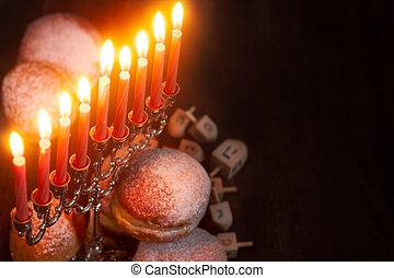 Symbols of jewish holiday hanukkah - menorah, donuts sufganiyot and dreidels