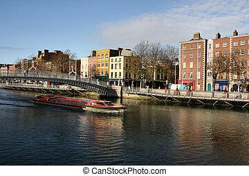 Ha'penny Bridge and Liffey river cruise boat in Dublin, Ireland. Typical view of Irish capital city.