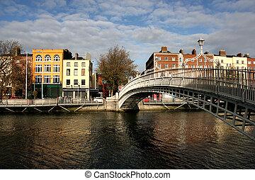Dublin landmark - Ha'penny bridge on Liffey River. Rows of colorful houses.