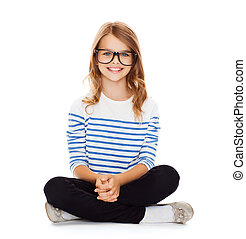 smiling girl in eyeglasses sitting on floor - happiness and ...