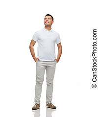 smiling man with hands in pockets looking up