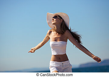 Happiness bliss freedom concept. Woman happy smiling joyful with arms up dancing on beach in summer during holidays travel.