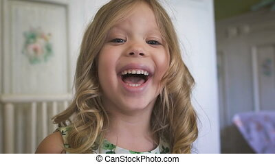 Happiness. Childhood. A beautiful little girl is smiling in the bright room. A little blondie enjoying her day indoors.