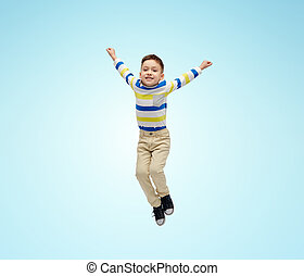 happy little boy jumping in air over blue