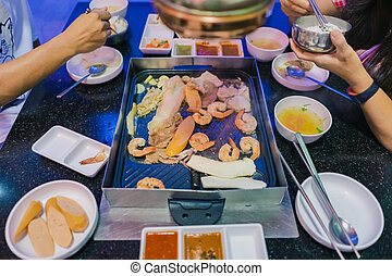 Happiness Enjoy eating Korean BBQ traditional famous food with family in a Korean restaurant