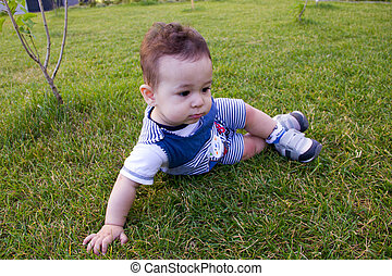 Happiness funny Baby boy sitting on the grass in the field. little in the spring or summer park the in sunshine day.