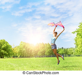 Happiness girl jumping on the green fields at beautiful...