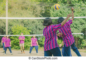 Happiness group of teenage friends playing volleyball in school.