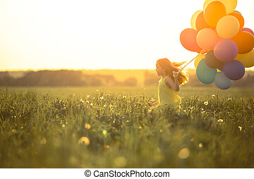 Happiness - Happy girl with balloons in the field