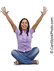 Happy young woman sitting with her legs crossed and arms in the air isolated against a white background.