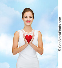 smiling woman in white dress with red heart