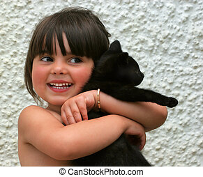 Young girl smiling and holding a black kitten in her arms.