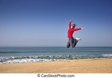 Happiness jump - Young woman jumping for fun in a beautiful...