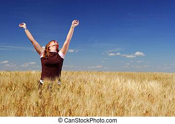 Happy woman in durum wheat field, brilliant summer sky.
