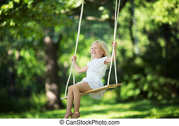 Happiness - Little smiling girl on a swing