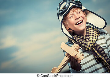 Happiness - Laughing boy with plane on the background of sky