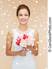 smiling woman in white dress with bunch of flowers