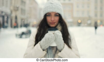 happiness, winter holidays, christmas, beverages and people concept - smiling young woman in white warm clothes with and drinking coffee to take away over snowy city background