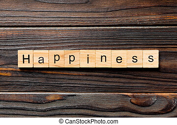 Happiness word written on wood block. Happiness text on wooden table for your desing, Top view concept