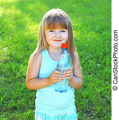 Happpy smiling child and plastic bottle with water on the grass summer