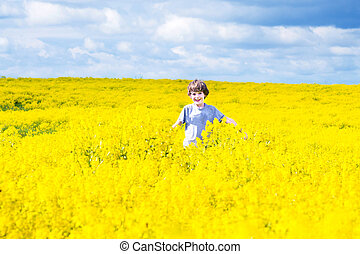 Happt laughing child running in a field of yellow flowers