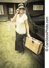 Happy 1920s Dressed Girl Holding Suitcase Next to Vintage Car