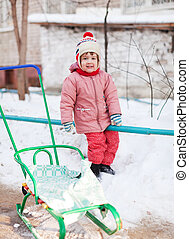 child with sled in winter park