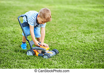 Happy 3 year old boy having fun mowing lawn