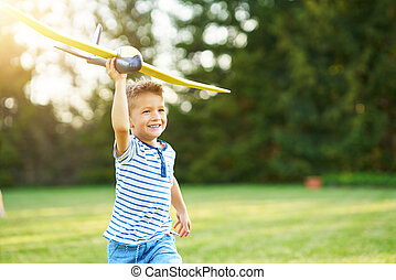 Happy 3 year old boy having fun playing with big plane outdoors