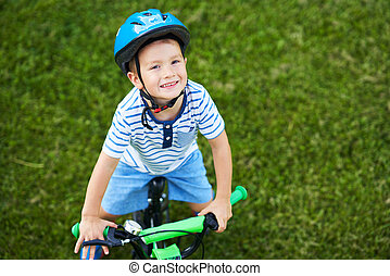 Happy 3 year old boy having fun riding a bike
