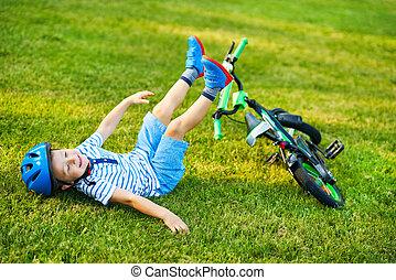 Happy 3 year old boy having fun riding a bike