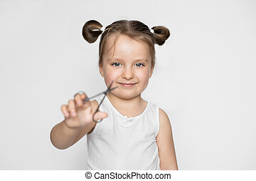 Happy 3 years old kid girl holding scissors for trim child's fingernails, smiling to camera. Baby nails hygiene concept. Close up, isolated on white. Focus on baby's face