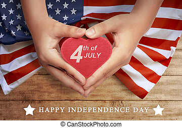 Happy 4th of July sign on heart at people hand
