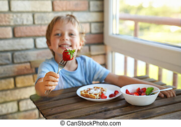 Happy 5 year old caucasian boy eat for Breakfast Viennese waffles with ice cream and strawberries