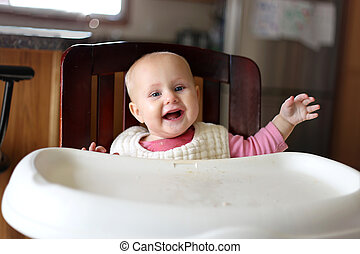 Happy 6 Month Old Baby Girl in Bib Eating at High Chair